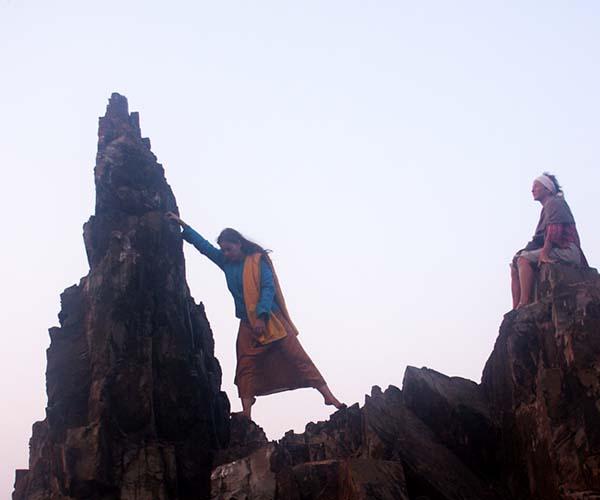 Woman climbing rock in Arambol beach, Goa