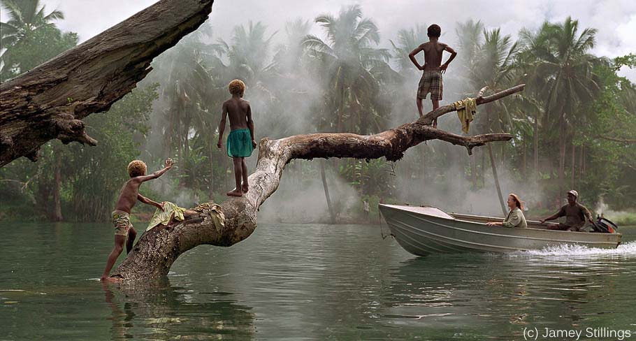 Boat on river with children in jungle (c) Jamey Stillings