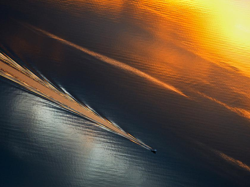 Boat in silver and golden sea.