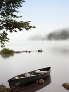 Boat in misty lake.