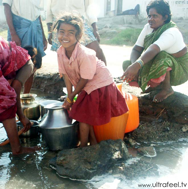 Indian people with steel sheet jugs collecting dirty water to drink! Seen in Tiruvannamalai, Tamil Nadu, India.