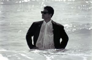 Man with wet suit in sea.