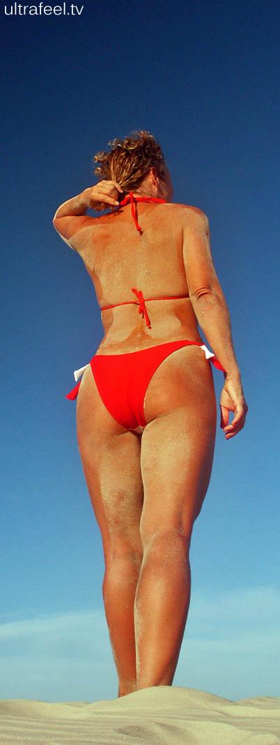 Goddess in red bikini in desert.