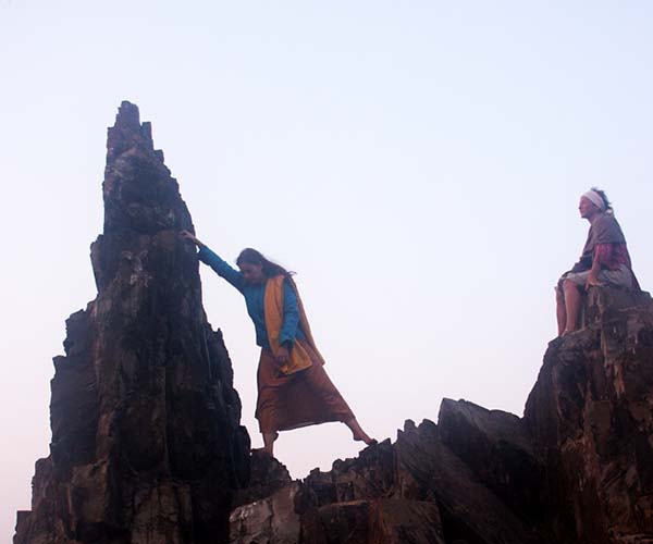 Woman climbing rock in Arambol beach, Goa
